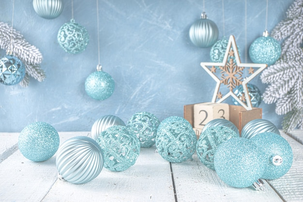 Festive christmas or winter decoration with blue silver xmas tree balls on light blue