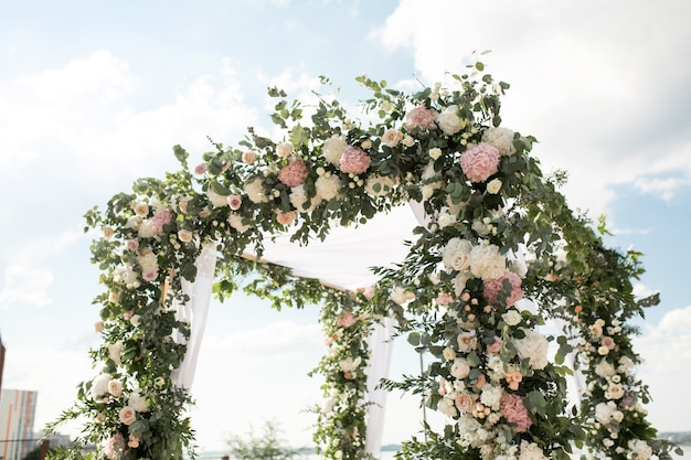 A festive chuppah decorated with fresh beautiful flowers for an outdoor wedding ceremony