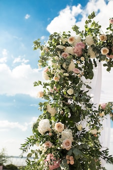 Festive chuppah decorated with fresh beautiful flowers for an outdoor wedding ceremony.