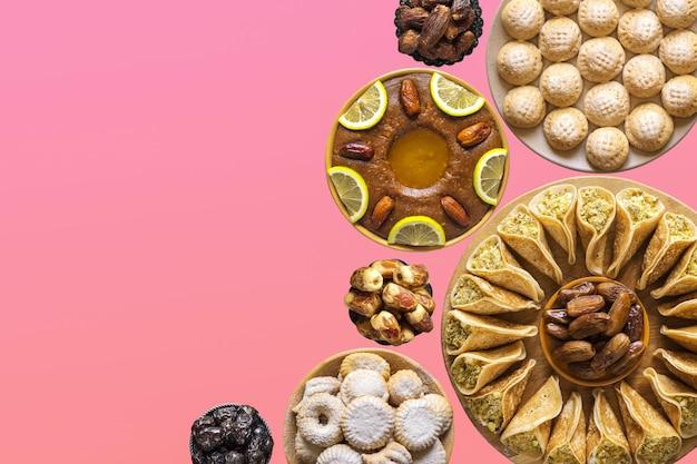 アラビア料理のさまざまな甘い料理とお祝いのコラージュ。テキストのコピースペース