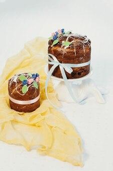 Праздничные красочные торты на пасху на бело-желтой ткани на белом фоне
