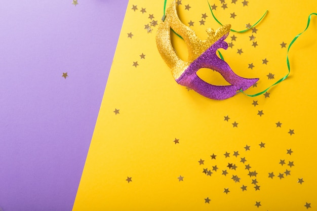 A festive, colorful group of mardi gras or carnivale mask on a yellow purple background. venetian masks.