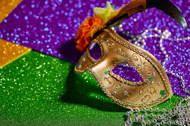 Festive, colorful mardi gras or carnivale mask and beads on golden. venetian masks. venetian carnivale celebration concept.