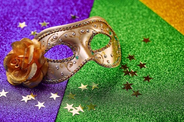 Festive, colorful mardi gras or carnivale mask on golden. venetian masks. venetian carnivale celebration concept.