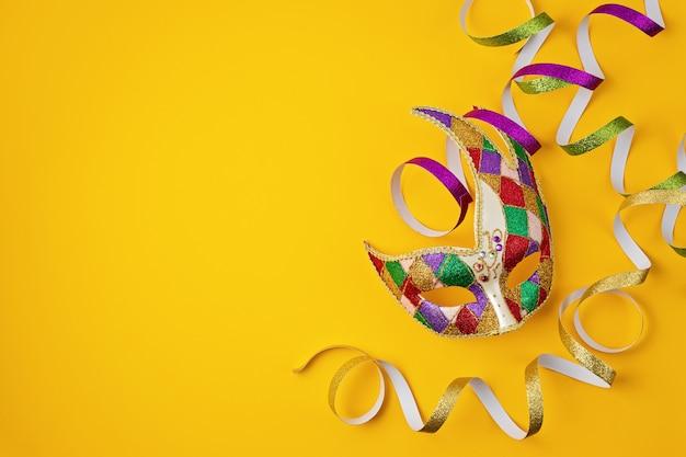 축제, 화려한 마디 그라 또는 카니발 마스크 및 노란색 벽 위에 액세서리. 평면 위치, 평면도, 복사 공간