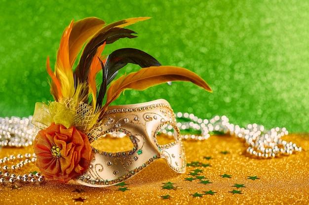 金色の背景に羽とビーズが付いたお祝いのカラフルなマルディグラまたはカーニバルマスクベネチアンマスクパーティの招待状グリーティングカードベネチアンカーニバルのお祝いのコンセプト