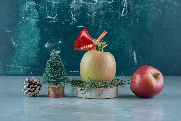 Composizione festosa di mele e addobbi natalizi su marmo.