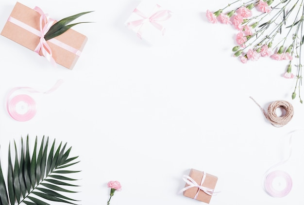 축제 구성 : 선물, 리본 및 흰색 테이블에 꽃 상자