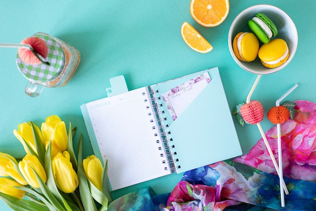 Праздничная композиция: коробки с подарками, лентами, цветами, ювелирной и бумажной тетрадью, вид сверху с копией пространства