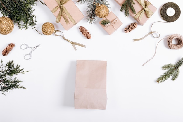Festive composition: boxes with gifts, ribbons, paper bag, christmas tree branches and cones, rope, scissors