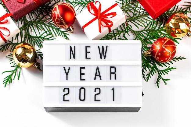 새 해 2021 축제 구성입니다. 빨간 리본 및 흰색 바탕에 황금 크리스마스 볼 선물 상자.