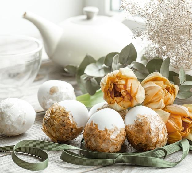Праздничная композиция на праздник пасхи с украшенными яйцами и живыми цветами.