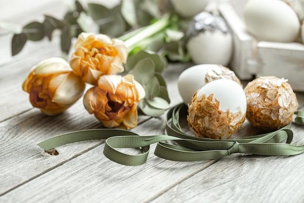 Праздничная композиция на праздник пасхи с декоративными яйцами и живыми цветами.