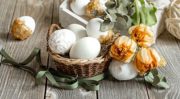 新鮮な春の花と卵でイースター休暇のためのお祝いの構成。イースターの装飾のコンセプト。