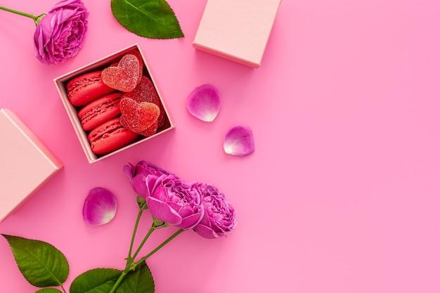 バレンタインデーと母の日のお祝いの作曲。ピンクのバラ、マカロンのギフトボックス