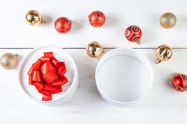Festive composition. gift boxes with red ribbon and christmas balls on a white background.