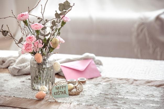 Composizione festiva buona pasqua con fiori in un vaso di vetro e dettagli decorativi sullo spazio della copia del tavolo