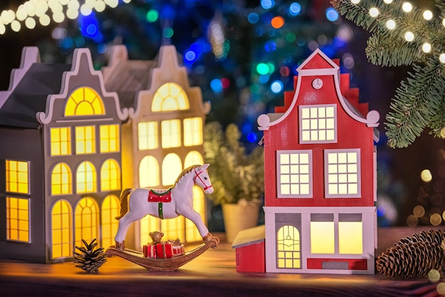 Festive composition of lamps in the shape of old european houses, a toy horse and pine cones