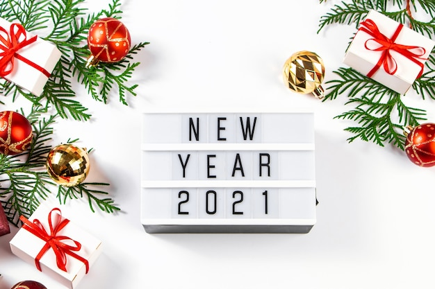 Festive composition for new year 2021. gift boxes with red ribbon and golden christmas balls on a white background.