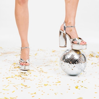 Festive composition of disco ball and legs