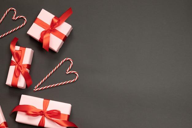 赤いリボンの装飾が施されたギフトボックスのお祝い組成、テキストのための場所で暗闇の中でキャンディー杖。