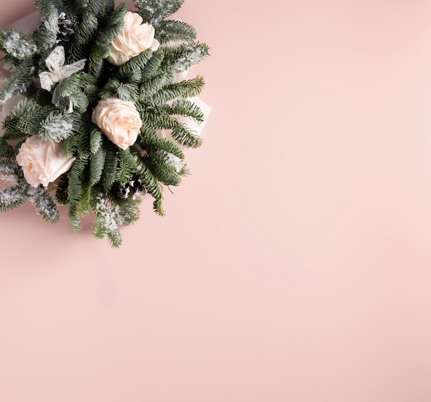 Праздничная композиция из роз и веток благородного на пудровом фоне