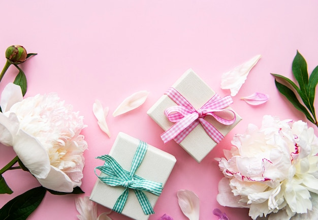ピンクの背景にお祝いの構成:牡丹の花、ギフトボックス。上面図、コピースペース。