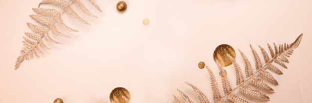 お祭りの構成。光沢のあるクリスマスの装飾的な花のシダの枝、紙吹雪、ベージュの背景にゴールドのキラキラ。フラットレイ。スペースをコピーします。ミニマリストスタイルのスタイリッシュな構成。