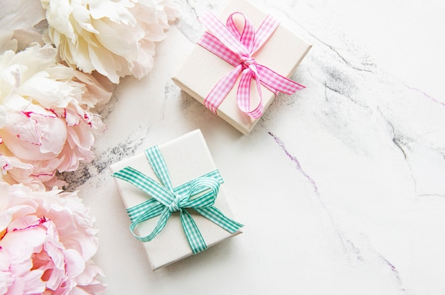 Festive composition on white background peonies flowers gift boxes top view copy space
