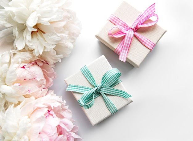 Festive composition on white background with peonies flowers, gift boxes.