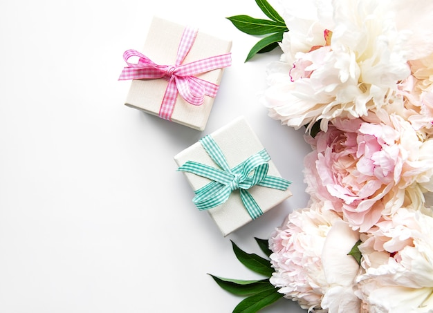 Festive composition on white, peonies flowers, gift boxes
