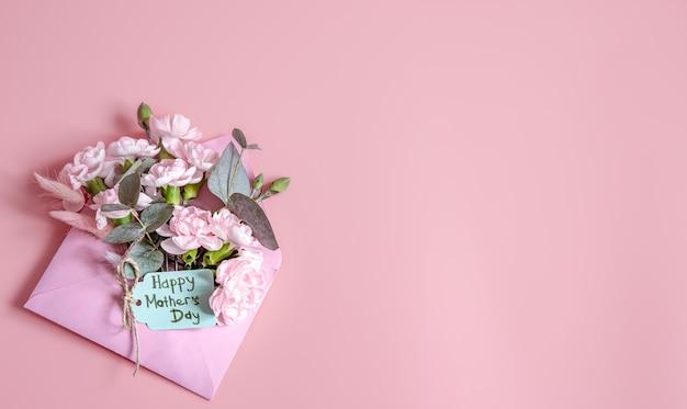 生花の入った封筒と幸せな母の日の碑文が平らに置かれたお祭りの構図。