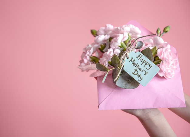 Праздничная композиция с конвертом с живыми цветами и надписью happy mother's day flat lay.