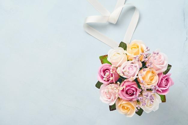 水色のテーブルの上のピンクの丸い箱の美しい繊細なバラの花とお祭りの構成。フラットレイ、コピースペース。