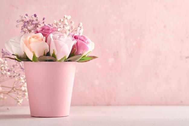 밝은 분홍색 배경에 분홍색 둥근 상자에 아름다운 섬세한 장미 꽃이 있는 축제 구성. 해피 어머니의 날 인사말 카드입니다. 정사각형 이미지.