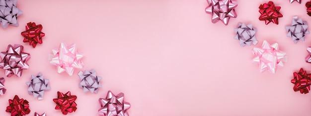 Праздничная композиция с украшениями различных розовых бантов на розовом фоне.