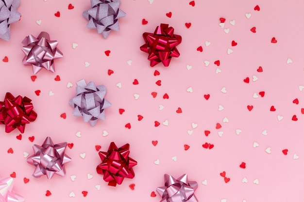 Festive composition with differrent pink bows decorations and small hearts on pink background.