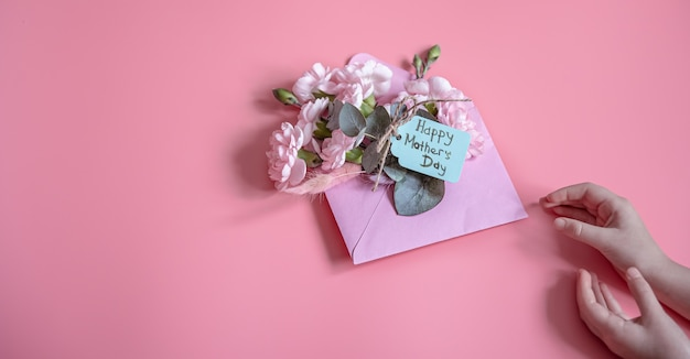 Festive composition with an envelope with fresh flowers and the inscription happy mother's day flat lay.