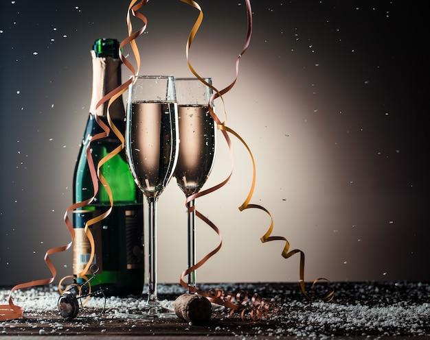 Праздничная композиция с открытой бутылкой шампанского и наполненными бокалами. изображение на темном фоне с подсветкой и копией пространства