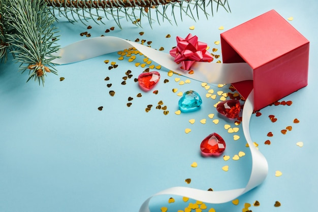 Festive composition with red box, ribbon, glass hearts, confetti and fir branches. gift concept for christmas and new year.