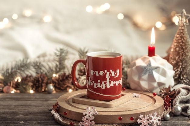 Festive composition with a red cup with inscription of merry christmas.