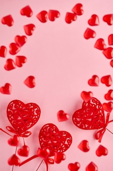 Праздничная композиция с тремя красными ажурными сердечками и маленькими летающими сердечками на розовом фоне. вид сверху, копия пространства. концепция дня святого валентина.