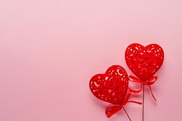 Праздничная композиция с двумя красными ажурными белыми сердечками на розовом фоне. вид сверху, копия пространства. концепция дня святого валентина.