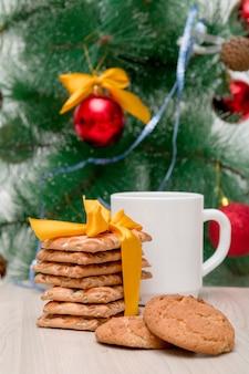 Праздничное печенье и белая чашка на фоне украшенной елки, новогодний фон, новый год 2020