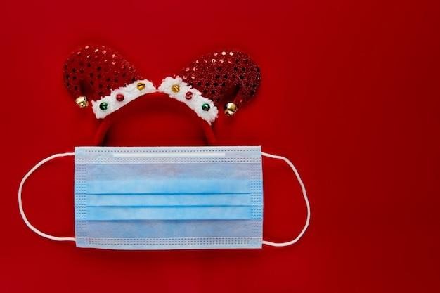 フェイスマスクと赤い背景の装飾から作られたお祝いのコロナウイルスエルフ。フラットレイ、トップビューのクリスマス休暇の構成。新年の壁紙バナー