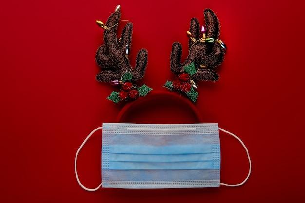 フェイスマスクと赤い背景の装飾から作られたお祝いのコロナウイルストナカイ。フラットレイ、トップビューのクリスマス休暇の構成。新年の壁紙バナー