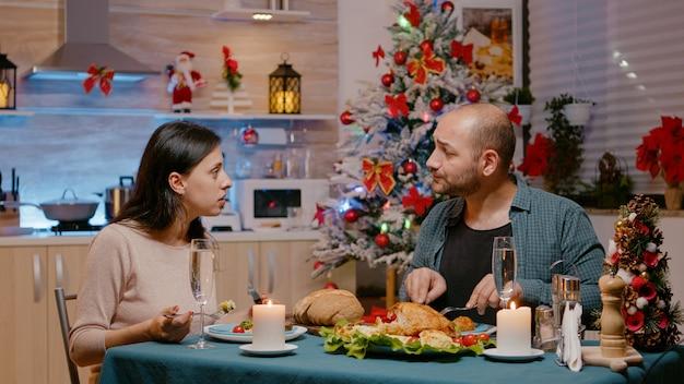 Festive couple enjoying christmas eve dinner with seasonal meal