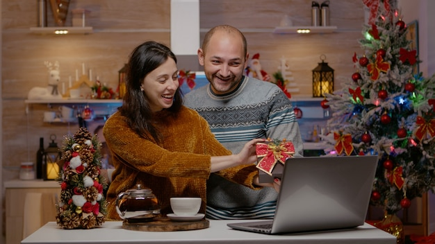 Festive couple giving presents on video call conference