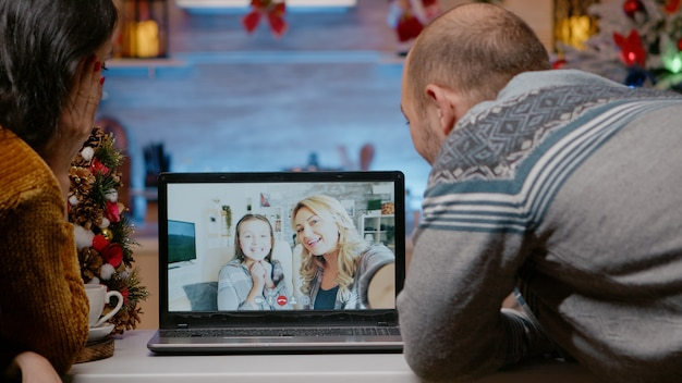 Festive couple talking to family on video call conference