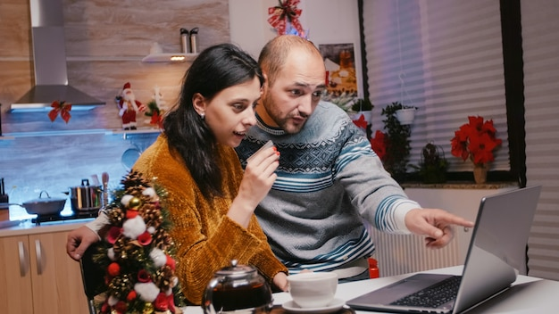 Festive couple using credit card for christmas shopping